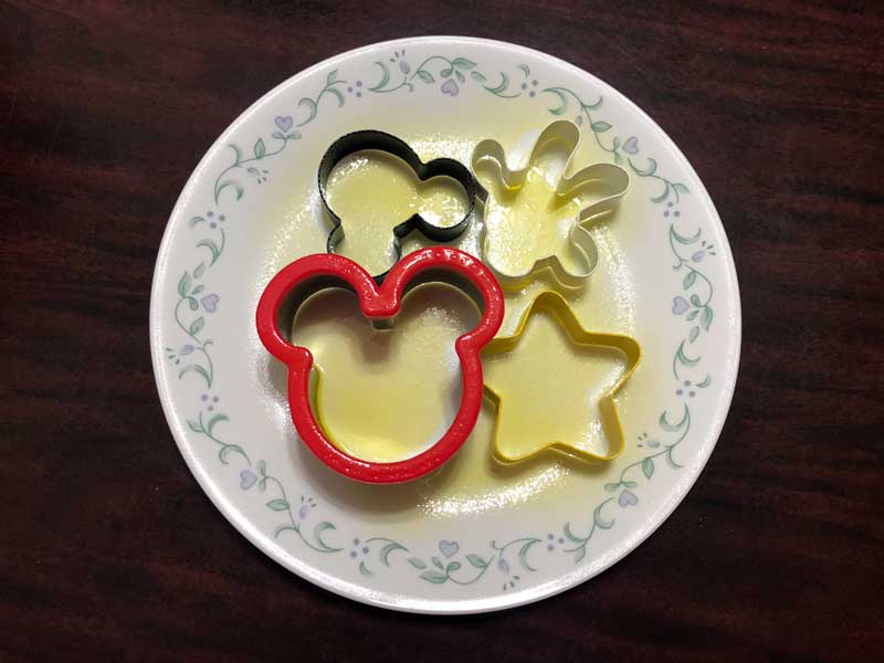 Disney themed cookie cutters on plate with cooking spray